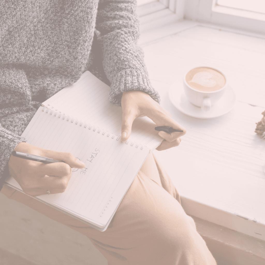 mulher escreve no papel motivos para se organizar